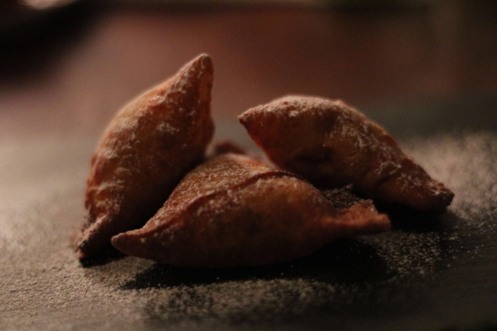 3 sweet samosa dusted with icing up close